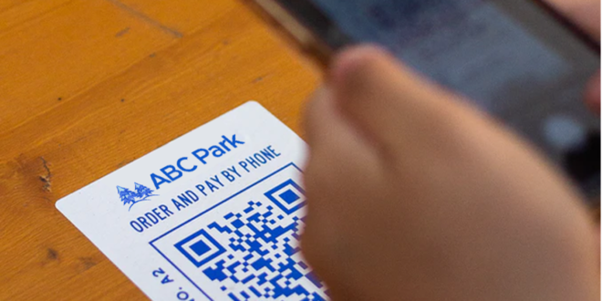 How do amusement parks maintain a touchless park experience with QR codes?